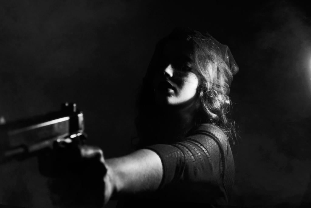 femme mettant un individu en joue avec une arme à feu de nuit