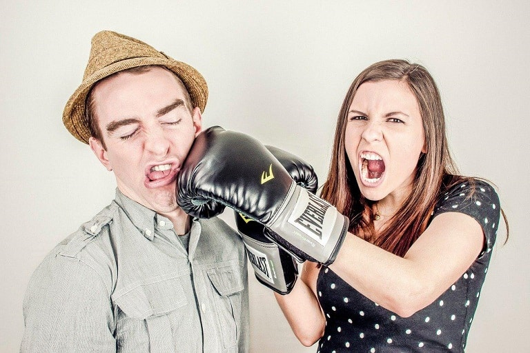 femme donnant un coup de poing avec un gant de boxe dans la mâchoire d'un homme