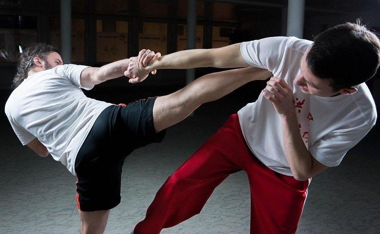 deux individus s'affrontant, l'un des deux plaçant un coup de pied au niveau de l'aisselle de son adversaire