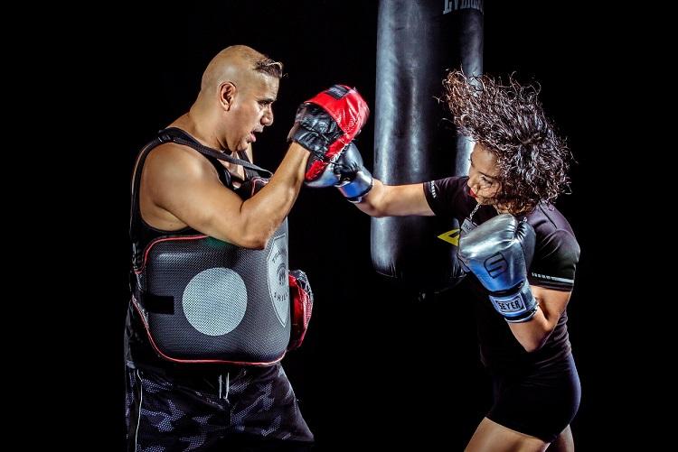 sparring avec un partenaire d'entraînement équipé de deux pattes d'ours dans chaque main et d'un plastron, le deuxième s'entraînant à frapper les cibles avec des gants de boxe