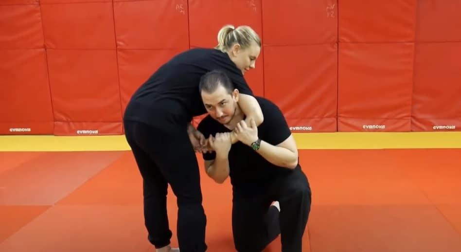 agresseur effectuant un étranglement guillotine et victime se dégageant de la prise, les deux mains agrippant l'avant-bras